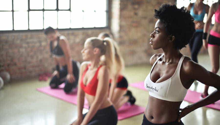 Girls doing yoga in a gym.