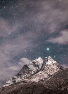 Night photo of a big mountain peak with starts behind it.