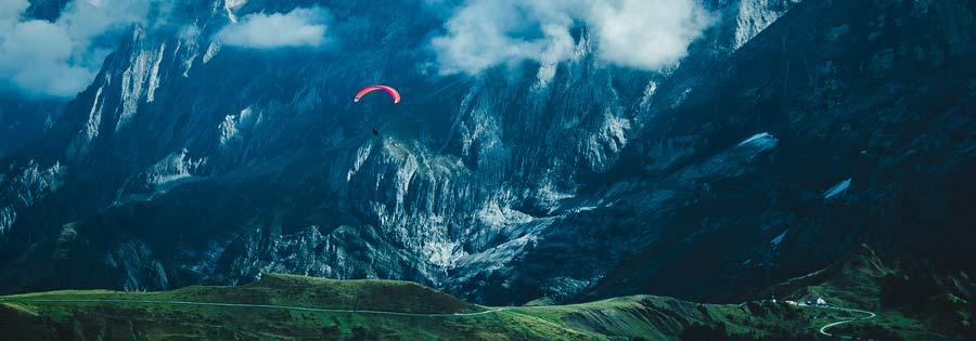 Person paragliding  against big mountains.