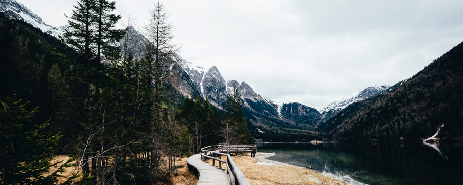 Wooden path next to a lake leading towards mountains with snowy peaks.