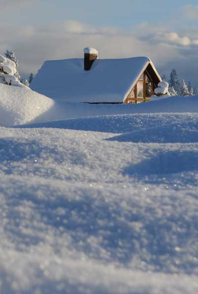 Snow covered cabin during the winter.
