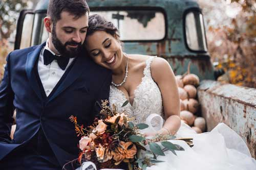 Wedding photo of a couple in sitting on the back of a truck.