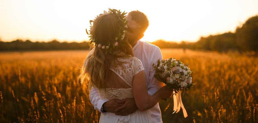 Newly weds kissing each other during sunset.