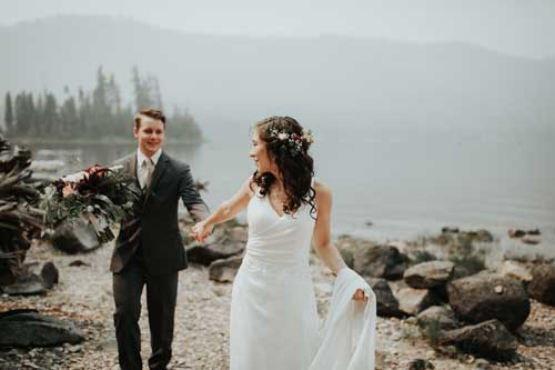 Wedding photo of a couple holding hands, and walking.