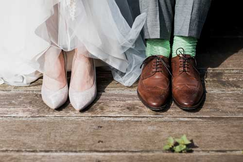 Closeup of couple's shoes during a wedding.